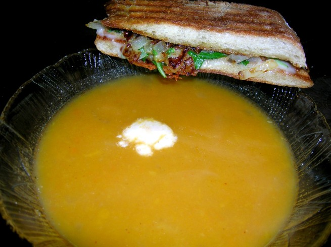 Butternut squash soup with caramelized onion, arugula, and Taleggio cheese panini