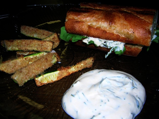salmon sandwich with dill dip and arugula, served alongside zucchini fries