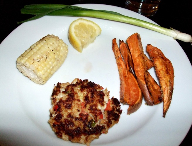 clockwise from right: sweet potato fries, crab cake, corn on the cob and green onion garnish.